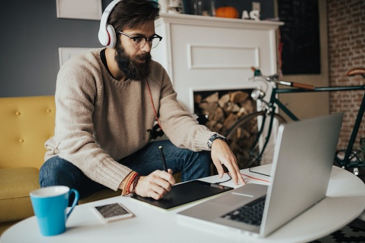 Young man working from home on his computer to earn money while working remotely